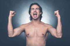 Everyday winner. Happy young shirtless man keeping eyes closed and gesturing while standing against grey background Stock Photos