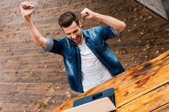 Everyday winner. Top view of excited young man keeping arms raised and expressing positivity while sitting at the wooden table outdoors Stock Photo
