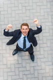 Everyday winner. Top view of happy young man in formalwear keeping arms raised and expressing positivity while standing outdoors royalty free stock photography