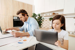 Everyone is doing their own thing. Work in harmony. Pleasant cute girl standing next to her father and looking at a tablet while her dad working with a pencil Royalty Free Stock Image