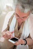 Everyone has a mobile phone today. Elderly well-dressed woman using a modern mobile phone Stock Photography