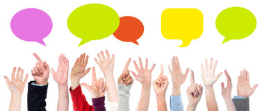 Everyone has something to say. Hands raised up. Colorful speech bubbles Stock Photo