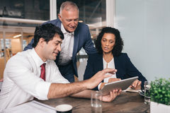 Everyone has something to work this out. Three diverse businesspeople talking together over a digital tablet while working at a table in an office boardroom Royalty Free Stock Photo