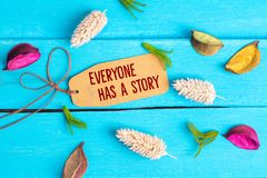 Everyone has a story text on paper tag. With rope and color dried flowers around on blue wooden background stock images