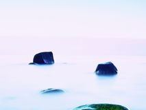 Everyone loves romantic atmosphere of sea. Peaceful sea level, stones in  water Royalty Free Stock Image