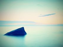 Everyone loves romantic atmosphere of sea. Peaceful sea level, stones in  water Stock Photography