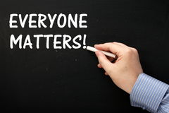 Everyone Matters!. Male hand wearing a business shirt writing the phrase Everyone Matters on a blackboard using white chalk stock images