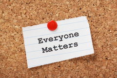 Everyone Matters. The phrase Everyone Matters typed onto a scrap of lined paper and pinned to a cork notice board royalty free stock photo