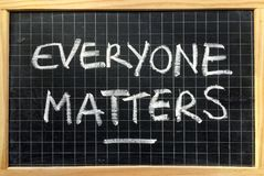 Everyone Matters. The phrase Everyone Matters written by hand in white chalk on a used blackboard as a reminder of equality for all royalty free stock photos