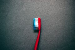 Red toothbrush on background sideways. Everyone needs brushes, if you want to keep your teeth healthy royalty free stock image
