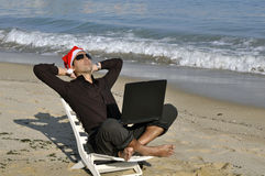 Everyone needs holiday. Young businessman with Christmass hat relaxing on the beach Stock Photos