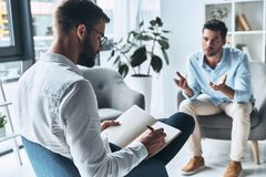 Everyone needs support. Young frustrated men speaking and gesturing while sitting on the therapy session with psychologist stock image