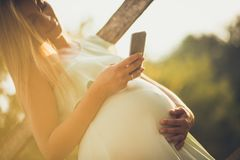 Everyone wants to know how they are both mother and baby. Pregnant woman standing outside and using smart phone. Close up royalty free stock images