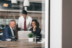 Everyone is working on this project. Three diverse businesspeople talking together over a laptop while working at a table in an office boardroom Stock Images