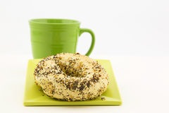 Everything bagel with fresh coffee in green mug Royalty Free Stock Image