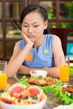 Everything is so boring!. Vertical image of a young girl being bored at the family dinner Stock Photo