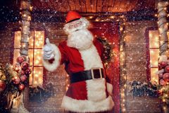 Everything is cool. Santa Claus is a builder. House of Santa Claus. Portrait of Santa Claus in a helmet on his head standing near his decorated house and shows stock photo