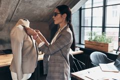 Everything must be perfect. Serious young woman in eyewear adjusting a collar of the jacket on mannequin while standing in her. Workshop royalty free stock image