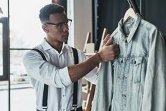 Everything must be perfect. Thoughtful young man touching denim. Jacket while standing in the showroom Royalty Free Stock Image