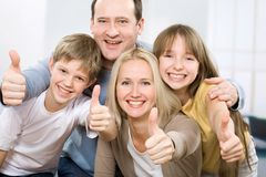 Everything is OK!. Cheerful family of four with their thumbs up Royalty Free Stock Image