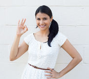 Everything is OK. Closeup portrait of young happy, smiling beautiful woman with pigtail giving OK sign with fingers, isolated white brick background. Positive Stock Image