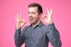 Everything is OK concept. Happy young man gesturing OK sign and smiling stock photography
