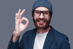 Everything is OK. Handsome young bearded man gesturing OK sign and smiling while looking at camera and standing against grey background Royalty Free Stock Photos