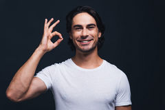 Everything is OK. Happy young man gesturing OK sign and looking at camera while standing against grey background Royalty Free Stock Image