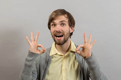 Everything is OK.Happy young man in shirt gesturing OK sign and smiling while standing Royalty Free Stock Photography