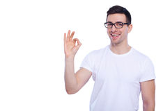 Everything is OK!. Happy young man in shirt and gesturing OK sign and smiling while standing against white isolated background Stock Photos