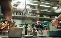 Is everything ok Surious chef is looking how his assistants are cooking a meat in a restaurant kitchen. Culinary school royalty free stock images