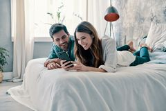 Everything is online. Beautiful young couple using smart phone and smiling while spending time in bed at home royalty free stock photos