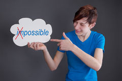 Everything is possible! Young man with sign in hand Stock Photography