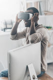 Everything is so real!. Handsome young African man adjusting his VR headset while sitting on the desk Royalty Free Stock Photos