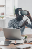 Everything is so real!. Handsome young African man in VR headset gesturing and smiling while sitting at the desk in creative office Royalty Free Stock Photography