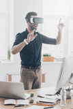 Everything is so real!. Handsome young man in VR headset gesturing and smiling while standing in creative office Stock Image