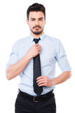 Everything should be perfect. Confident young man in shirt and tie looking at camera and adjusting his necktie while standing against white background Royalty Free Stock Photo