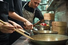 Everything should be perfect. Restaurant chef looking his assistants cooking a new dish in a kitchen. Cooking process stock photography
