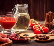 Everything on wood table for the preparation of acute Italian sa. Uce tomato garlic spices olive oil stock photo