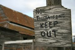 Everywhere a Sign. No trespassing sign on fence with abandoned barn in background royalty free stock photography
