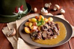 Everzwijnvlees met geroosterde aardappels, paddestoelen en Amerikaanse veenbessen Stock Afbeeldingen
