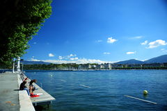 Evian Lack. A few persons are enjoying their leisure time beside Evian Lack in Geneva Royalty Free Stock Photography
