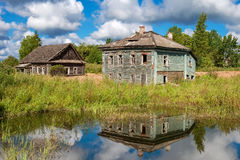 Evicted old wooden houses on the shore of muddy pond in the summ Stock Image