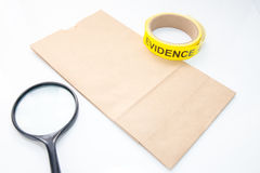 Evidence bag with evidence tape and magnifying glass for crime s Stock Photo