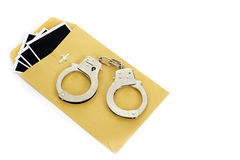 Evidence Handcuffs. A yellow envelope with pictures coming out of it with handcuffs sitting on top set against a white background royalty free stock photography