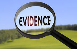 Evidence. Magnifying glass with the word evidence on blurred nature background. Searching evidence concept royalty free stock images