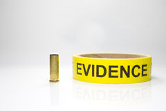 Evidence tape with brass bullet case on white background. Yellow evidence tape with brass bullet case on white background stock photos