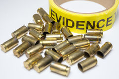Evidence tape with brass bullet cases focus on evidence word. Evidence tape with group of brass bullet cases on white background stock images