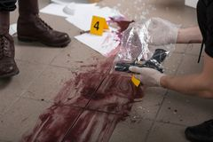 This evidence will lead us to a killer. Policeman holding evidence bag with a gun, close up of a bloody splash stock images