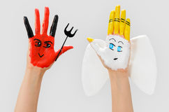 Evil and Angel Hands. Fun concept of evil and angel painted hands Royalty Free Stock Photo